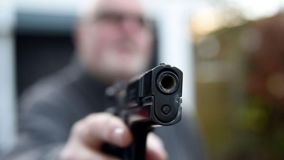 Symbolbild: Ein Mann hält eine Pistole in der ausgestreckten Hand und und zielt damit auf ein unbekanntes Ziel.
