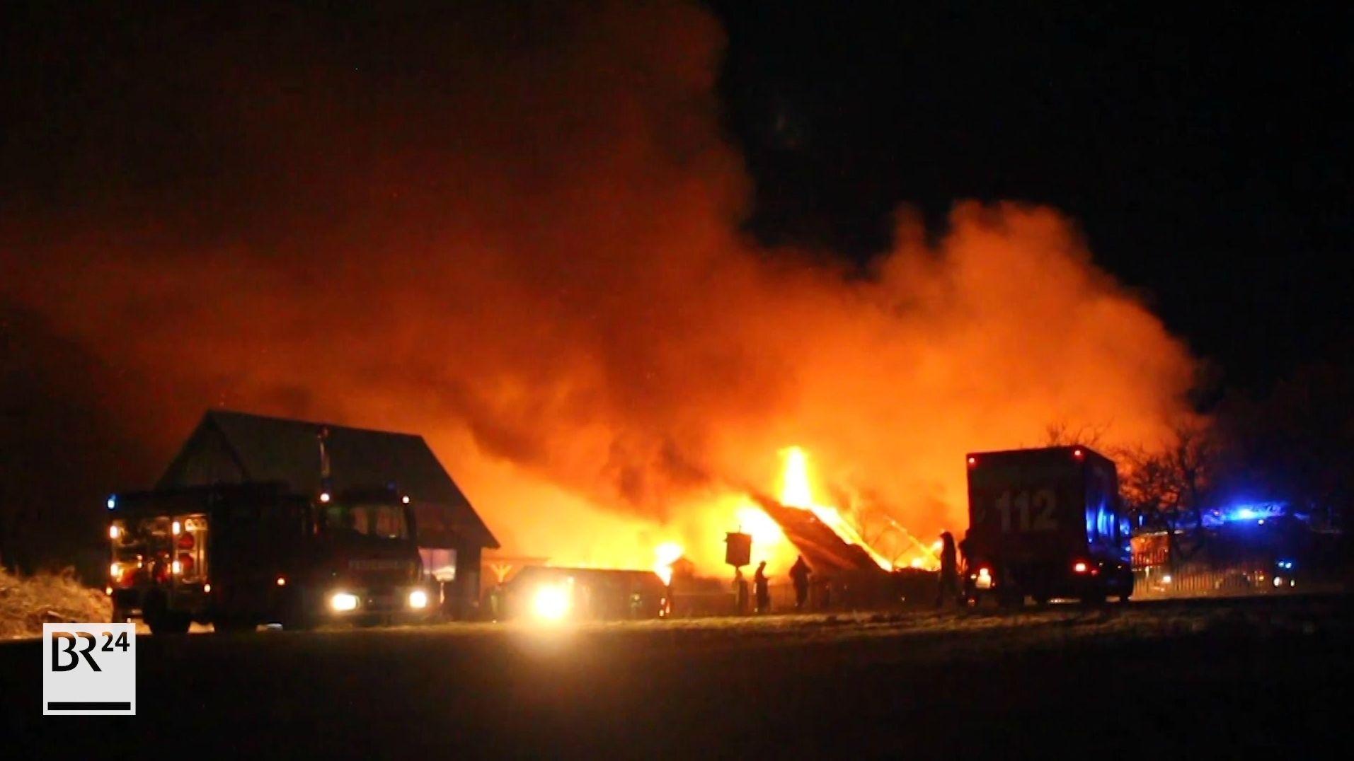 Lichterloh brennt ein Reiterhof, im Vordergrund mehrere Feuerwehrleute.