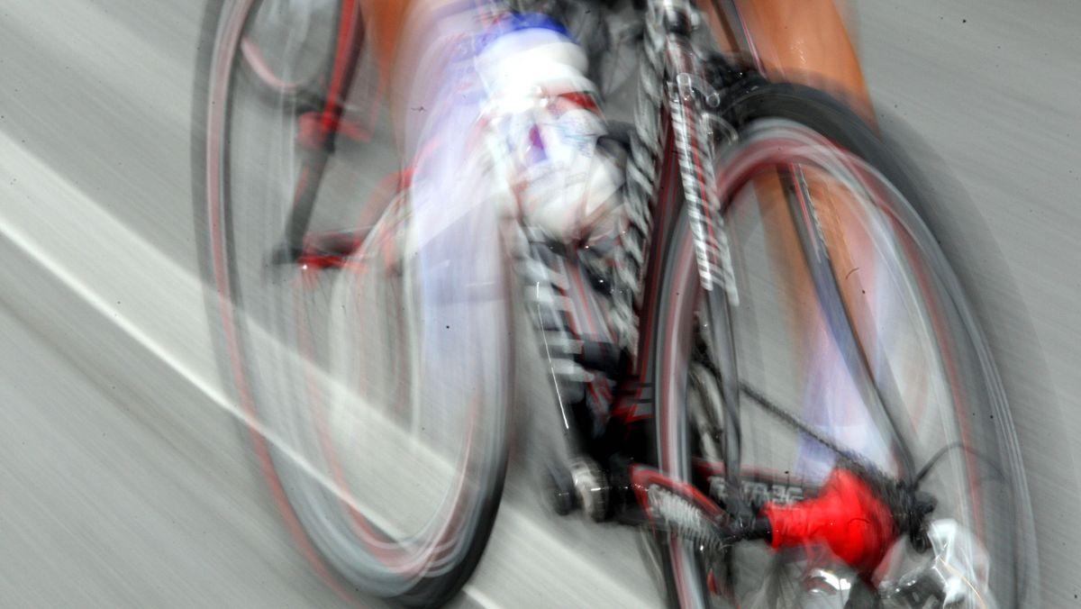 Ein Fahrer fährt mit einem Rennrad schnell über eine Straße.