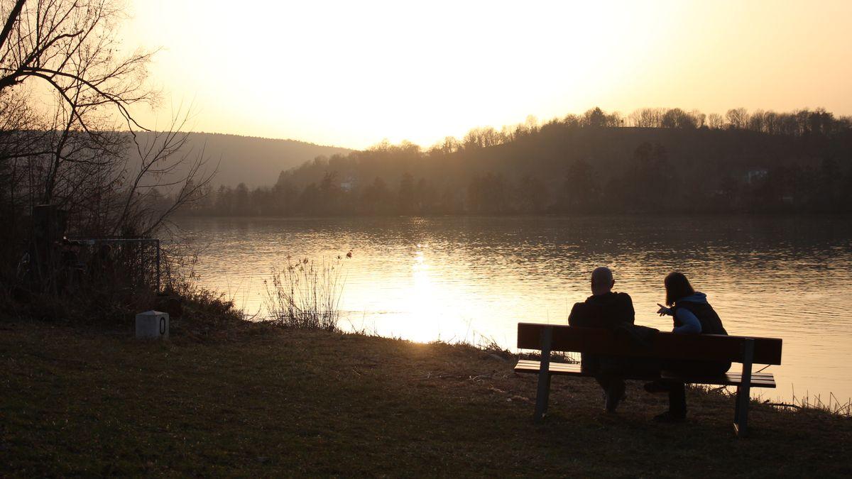 Ein Pärchen auf einer Bank am Flussufer