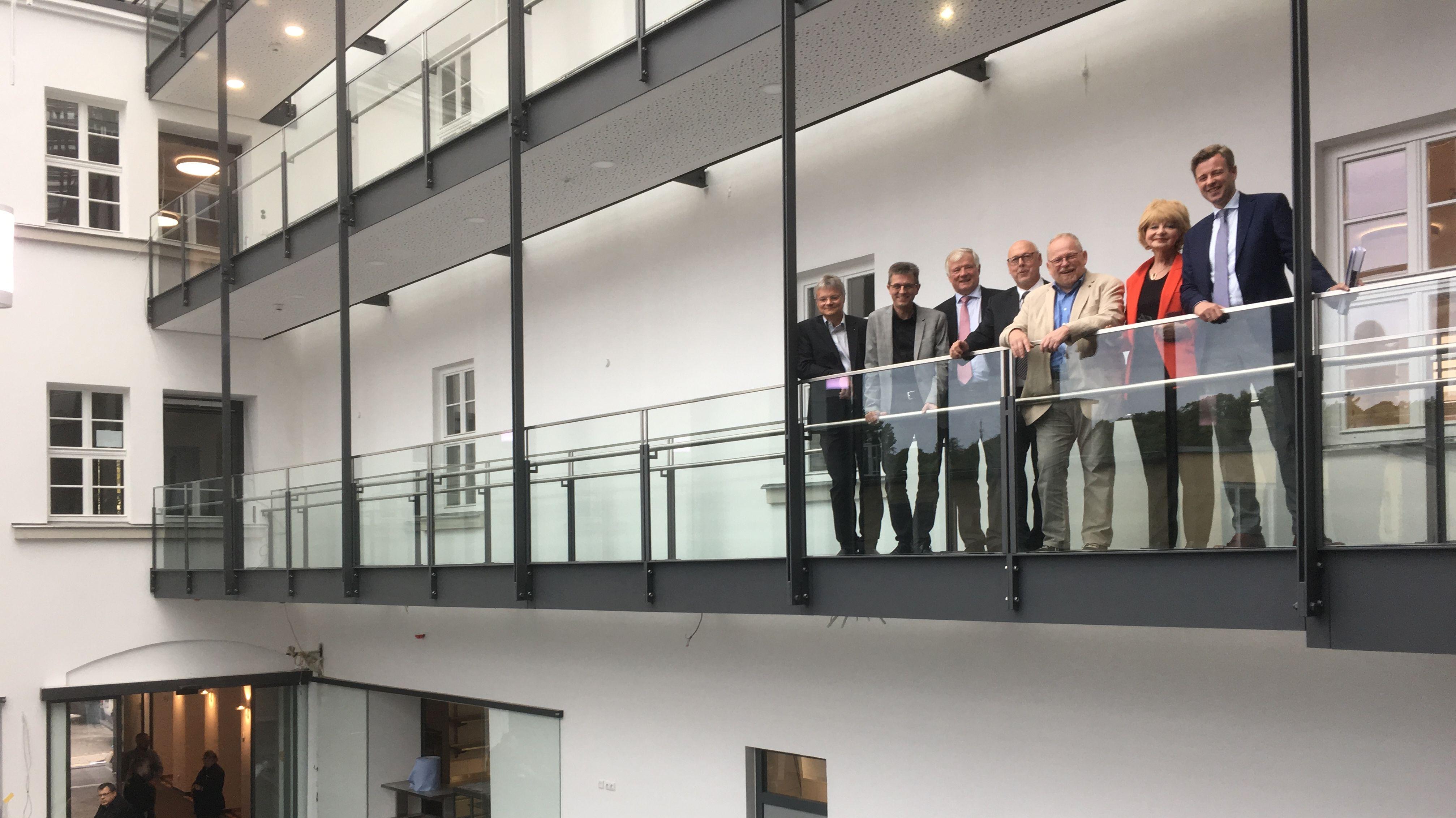 Landrat Oliver Bär und VHS Leiterin Ilse Emek gemeinsam mit VHS Vorständen im Inneren des neuen Gebäudes