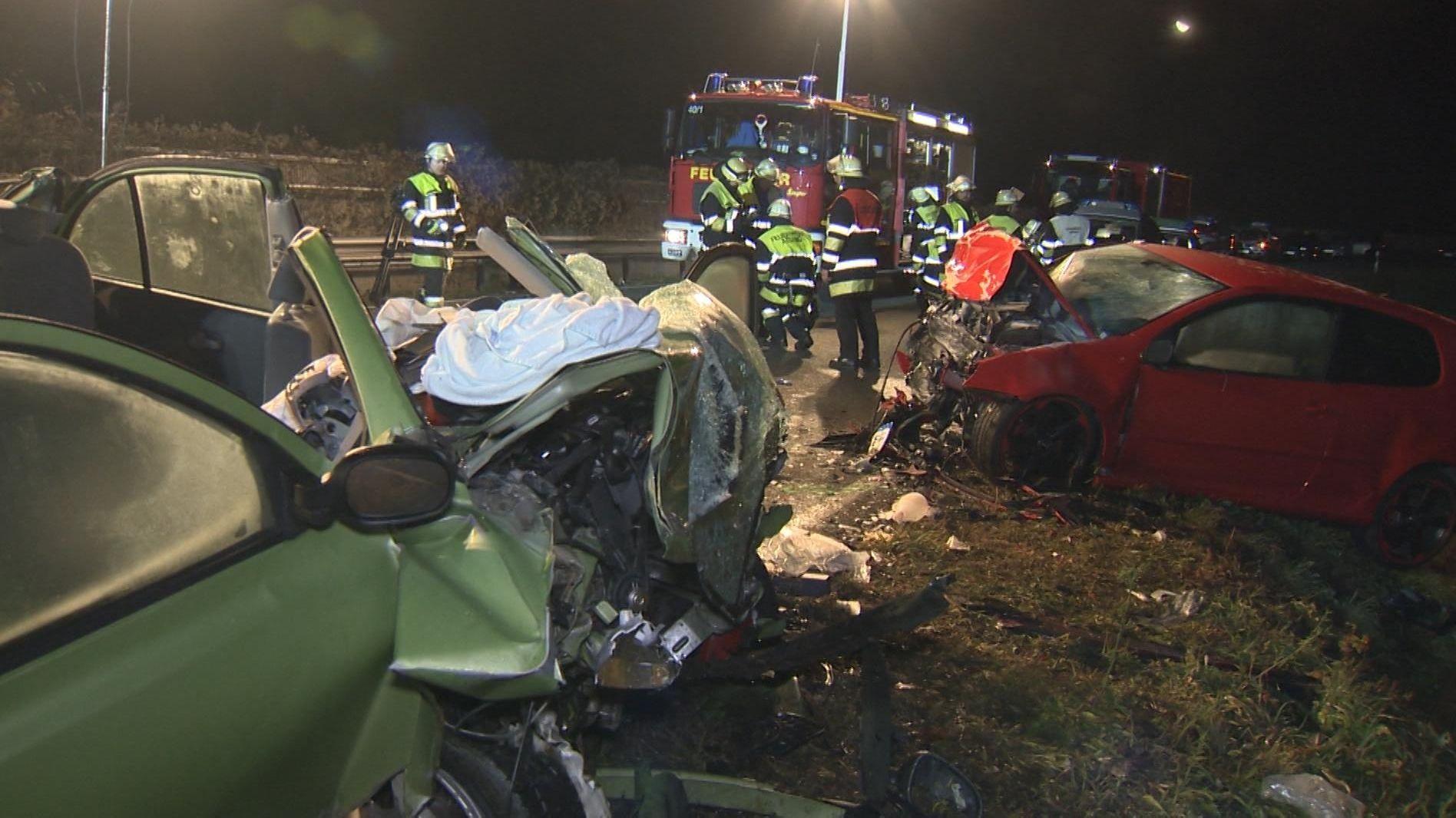 Feuerwehrleute an der Unfallstelle mit zwei zerstörten Autos