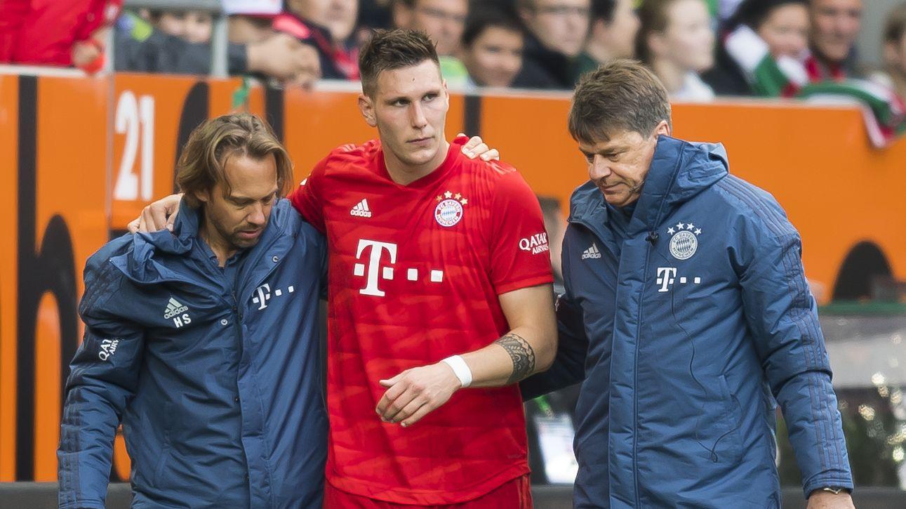 Niklas Süle wird nach seiner Verletzung von FC-Bayern-Betreuern vom Platz geführt