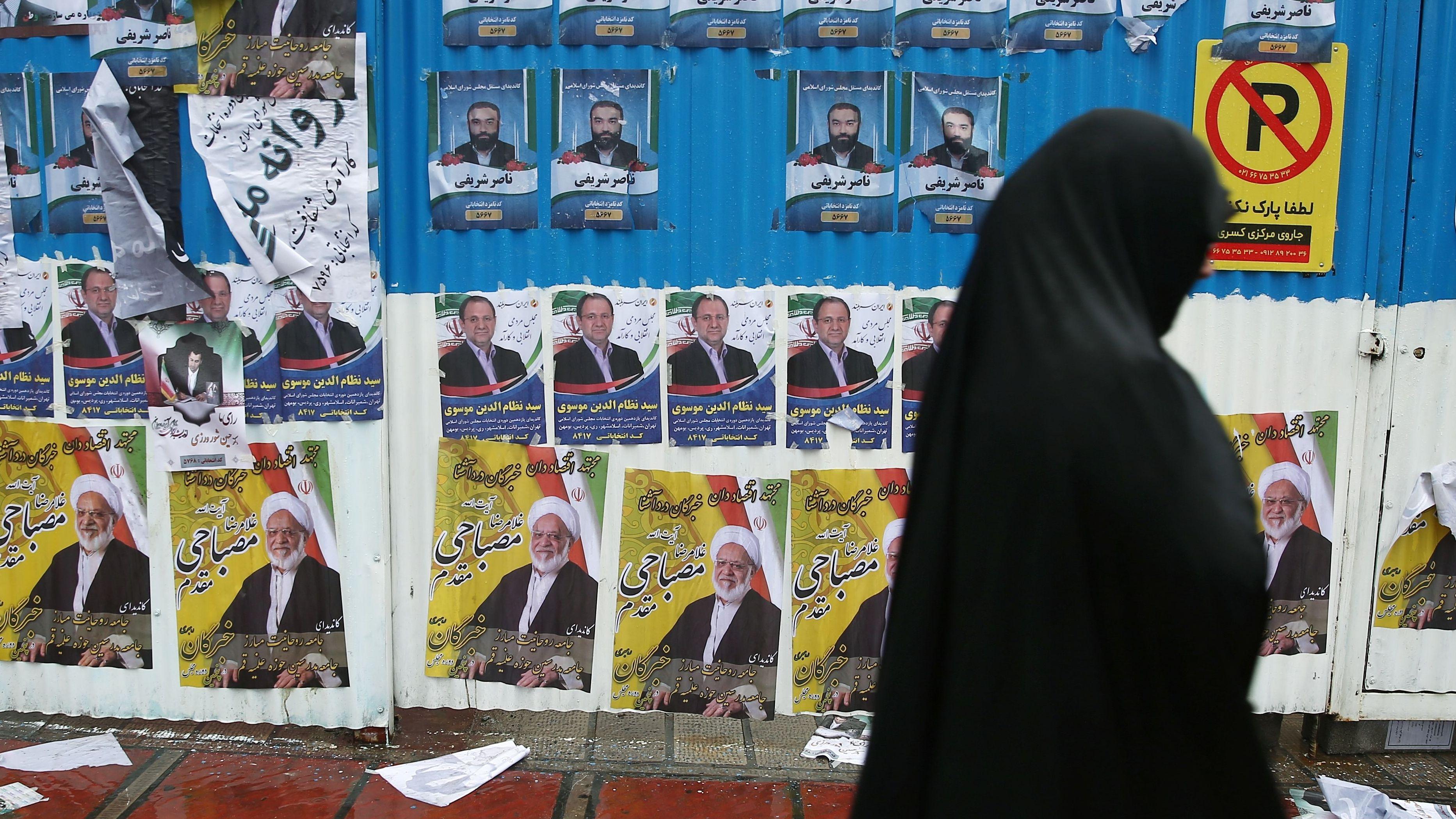 Eine Frau geht in Teheran an Wahlplakaten vorbei