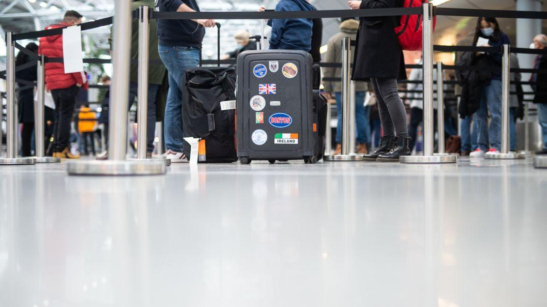 Eine Familie steht mit ihrem Gepäck am Flughafen in der Warteschlange