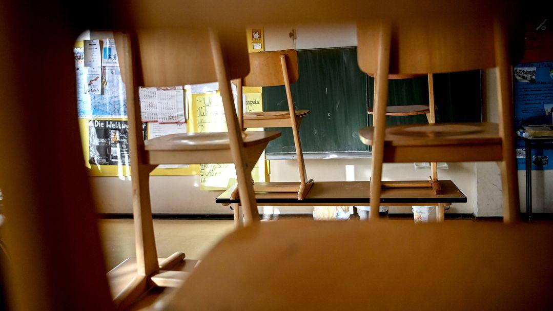 Ein leeres Klassenzimmer, in dem die Stühle auf den Tischen stehen. (Symbolbild)