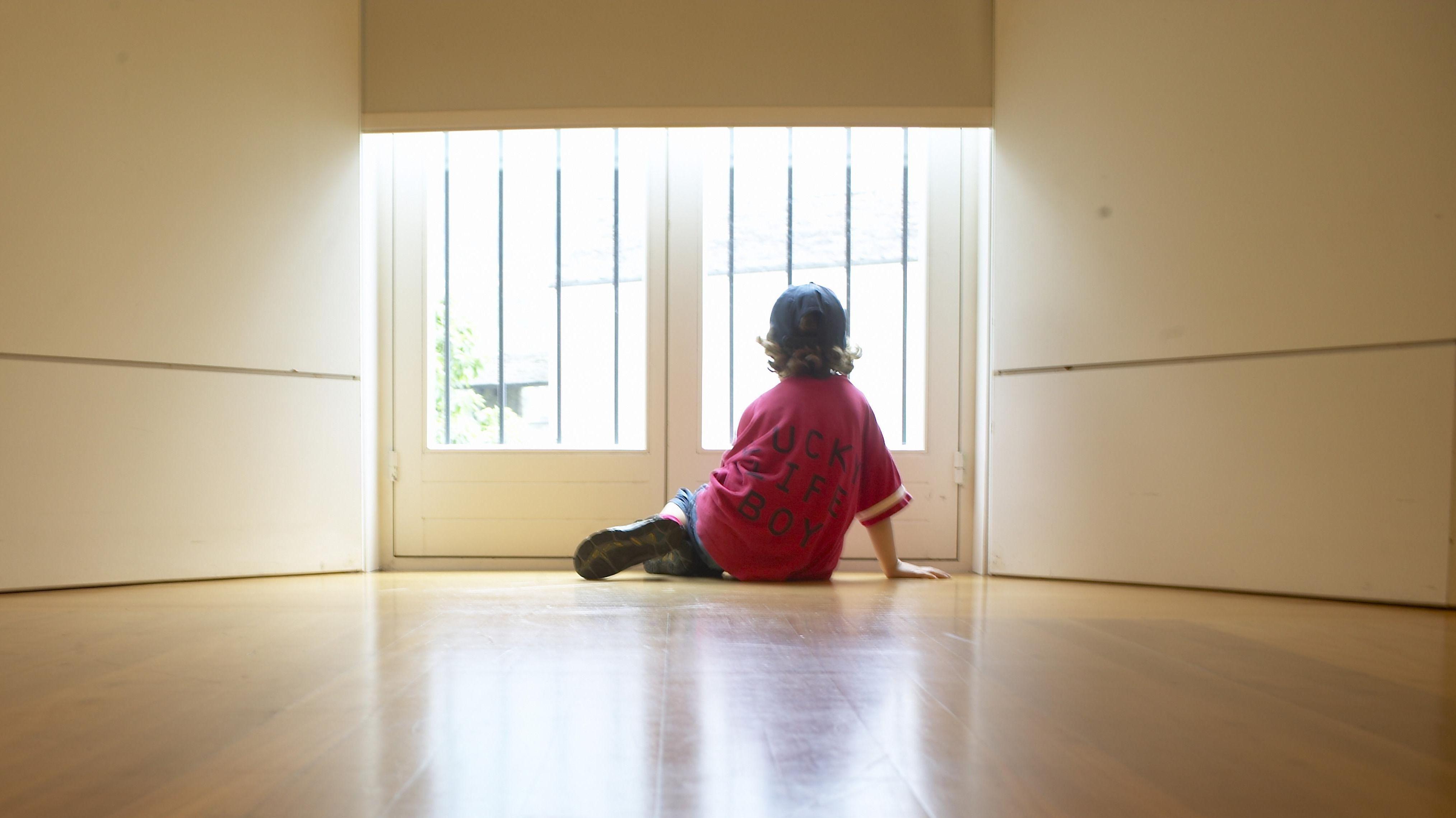 Junge sieht zu einer Glastüre hinaus