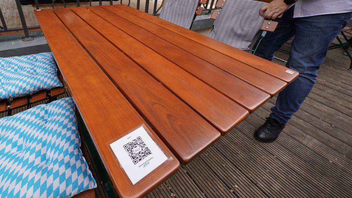 """Ein QR-Code der App Luca, mit der die Gäste nachverfolgt werden können, ist auf einem Tisch des Biergartens """"Zollpackhof"""" zu sehen."""