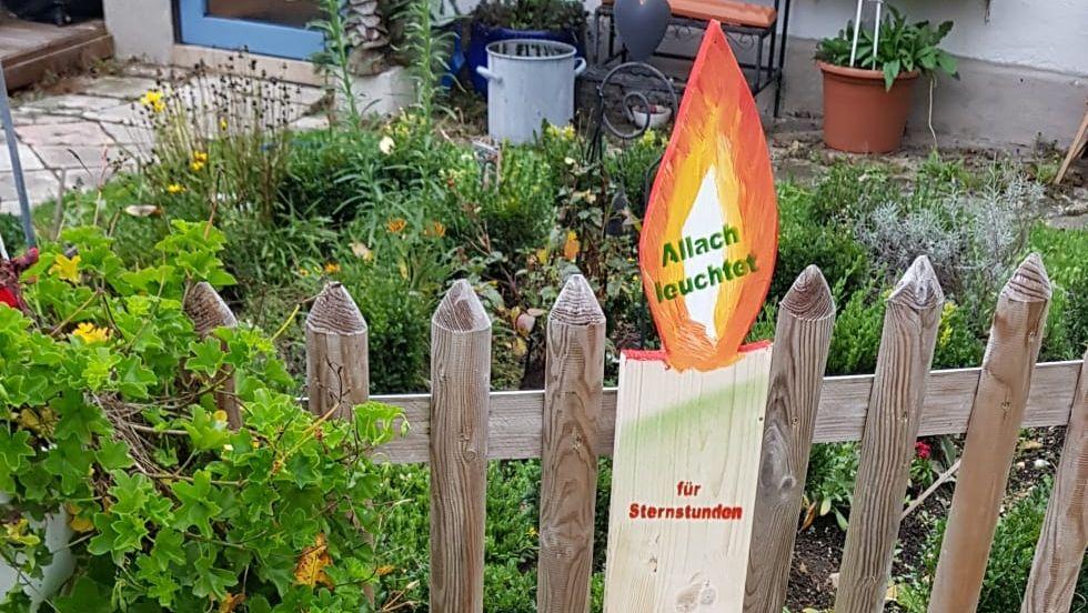 Kerze aus Holz am Gartenzaun