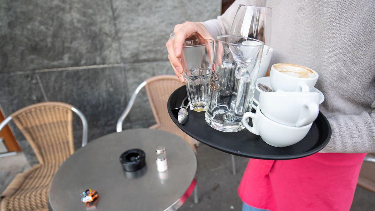 Ein Kellner räumt einen Tisch in einem Restaurant ab.