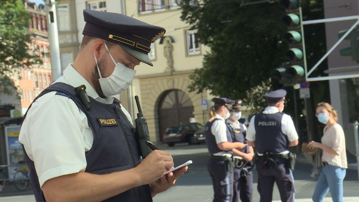 Polizisten kontrollieren die Einhaltung der Maskenpflicht in Würzburg.