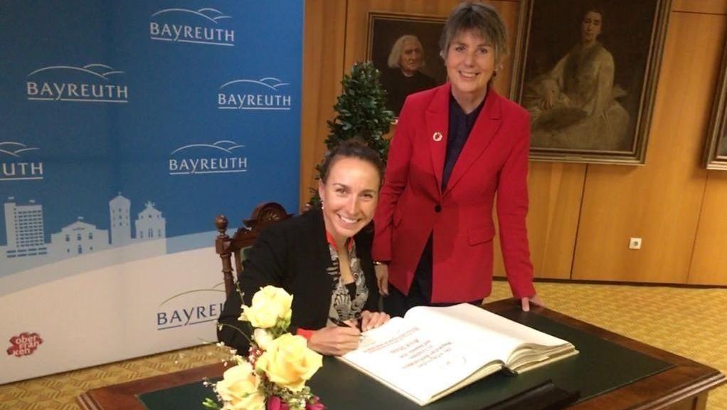 Anne Haug sitzt an einem Tisch und schreibt in das Goldene Buch. Bayreuths Oberbürgermeisterin Brigitte Merk-Erbe steht dahinter.