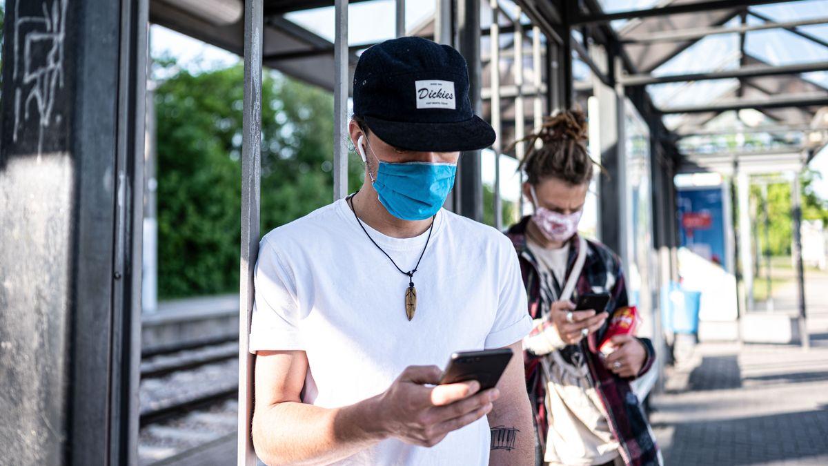 Jugendliche mit Maske spielen mit ihrem Smartphone