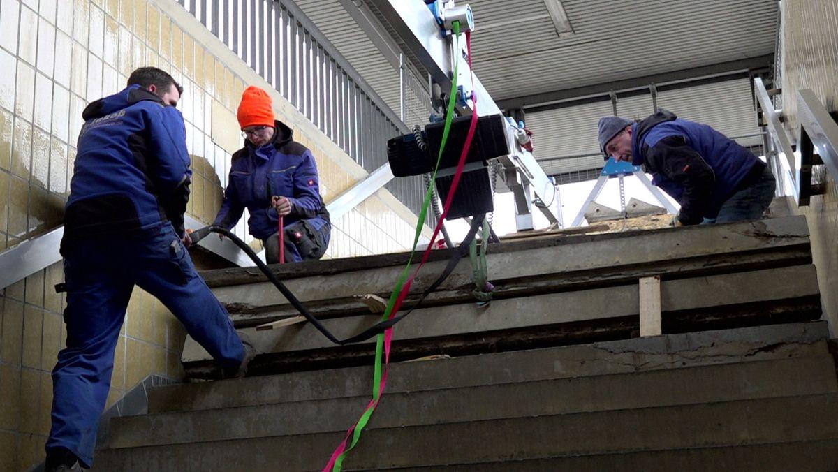 Arbeiter erneuern kaputte Treppenstufen am Bahnhof Kulmbach