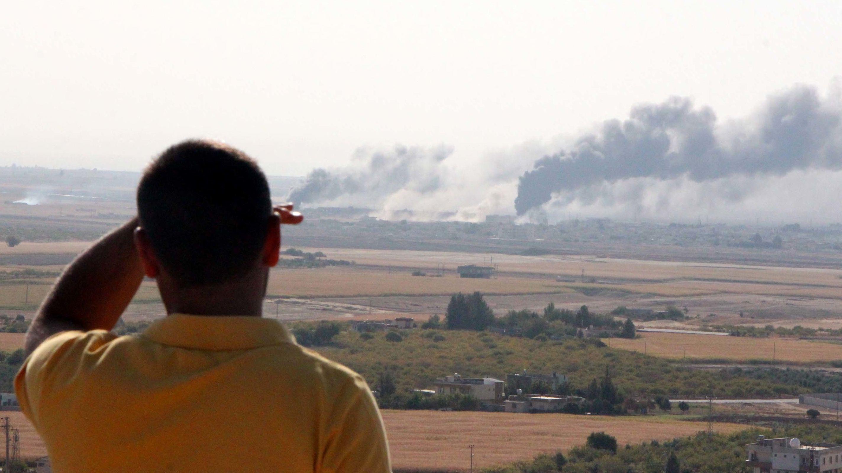 Ein Mann blickt auf die Stadt Ras al-Ain, aus der Rauchschwaden aufsteigen.