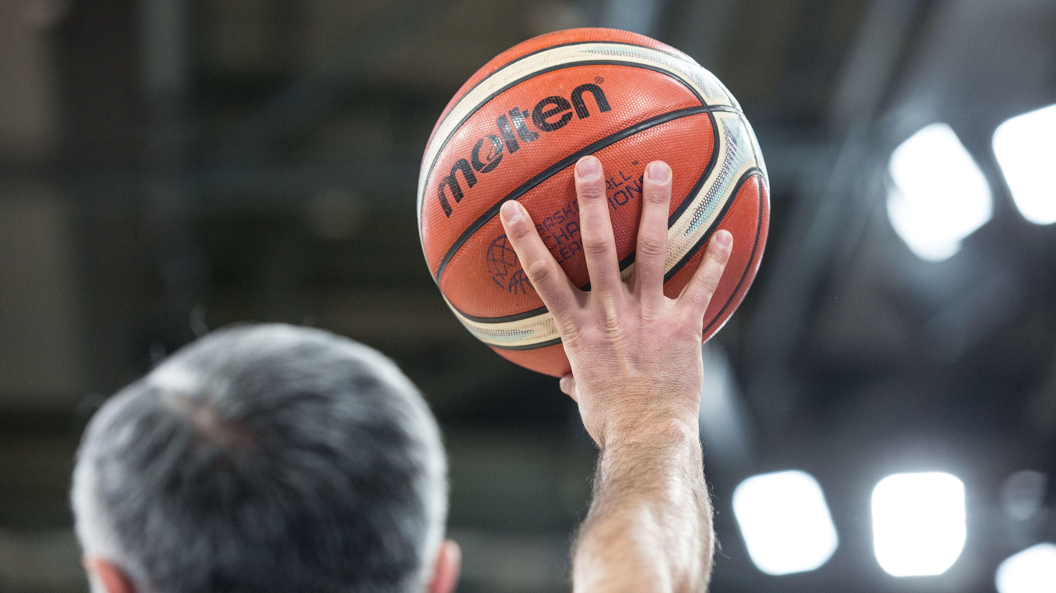 Mann hält Basketball in die Höhe