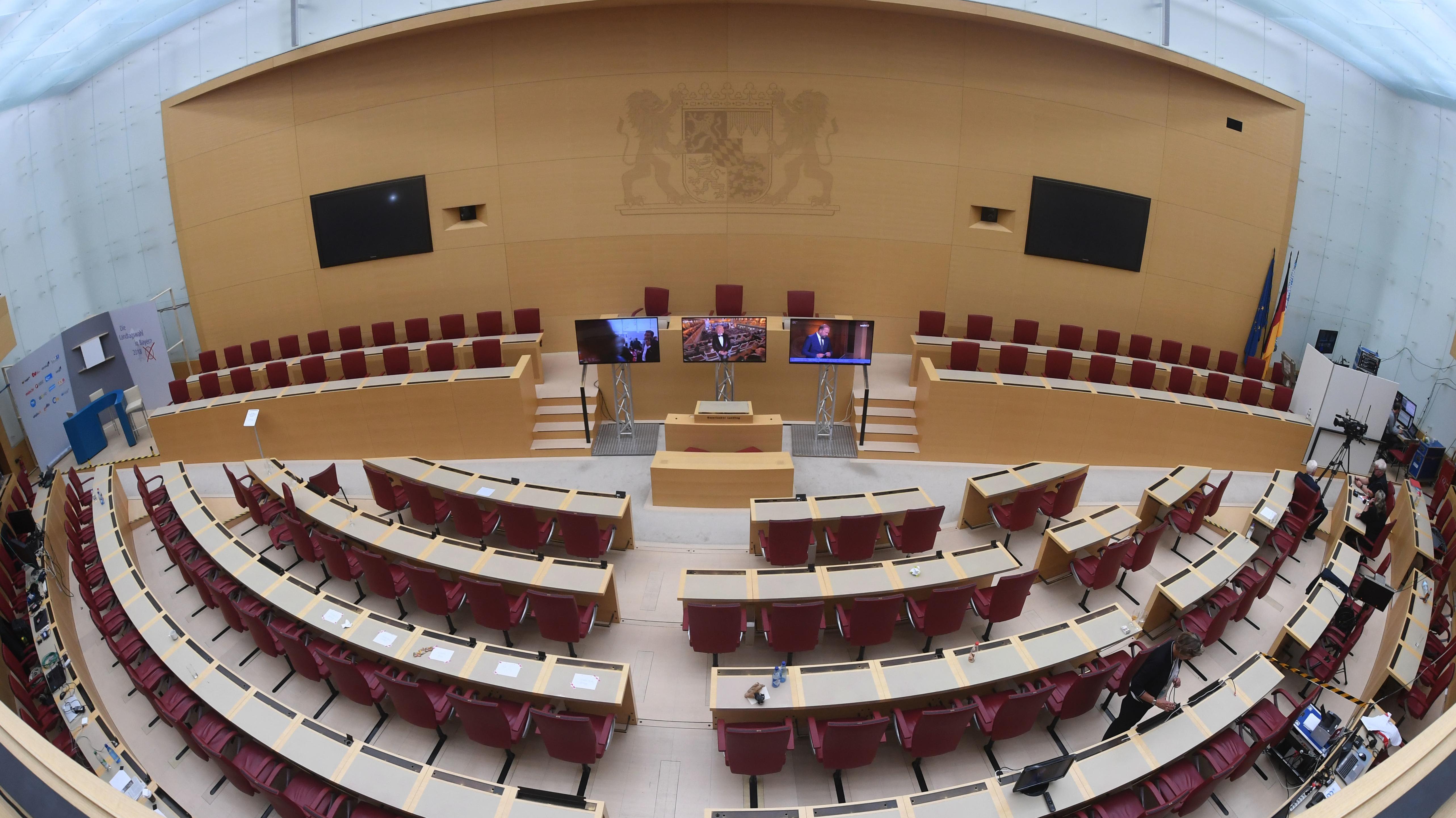 Leere Stuhlreihen und Monitore stehen im Sitzungssaal des Bayerischen Landtags.