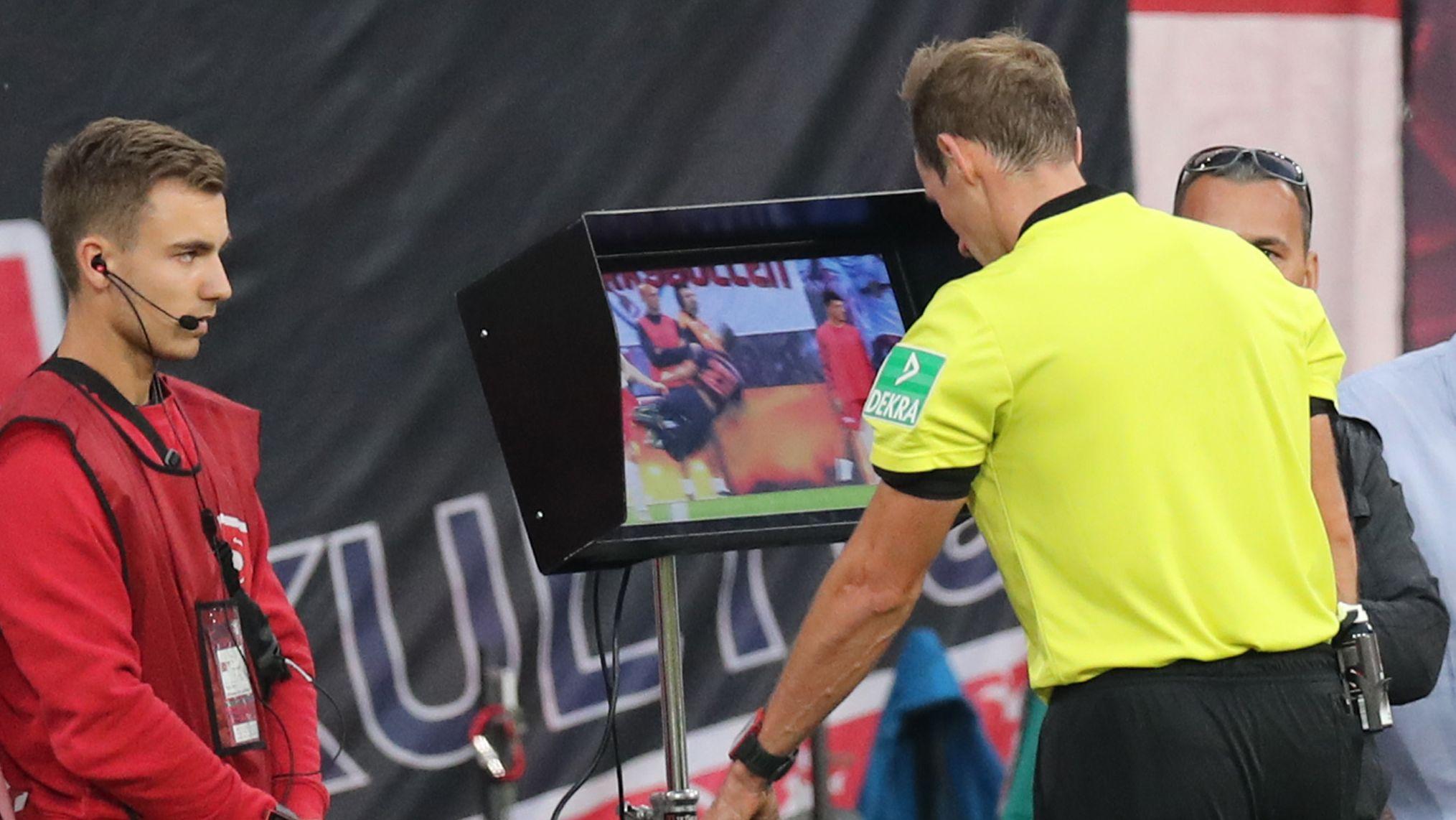 Ein Schiedsrichter sieht sich eine strittige Szene am Spielfeldrand an