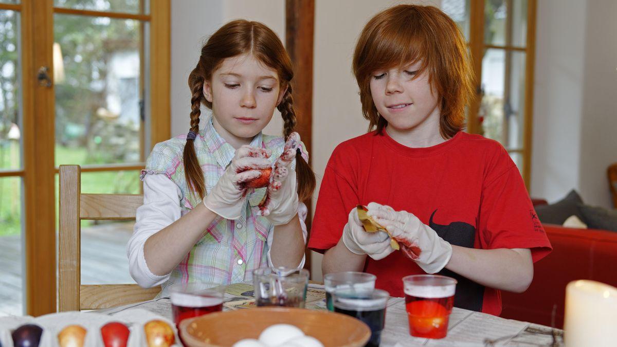 Zwei Kinder sitzen am Tisch und färben Ostereier