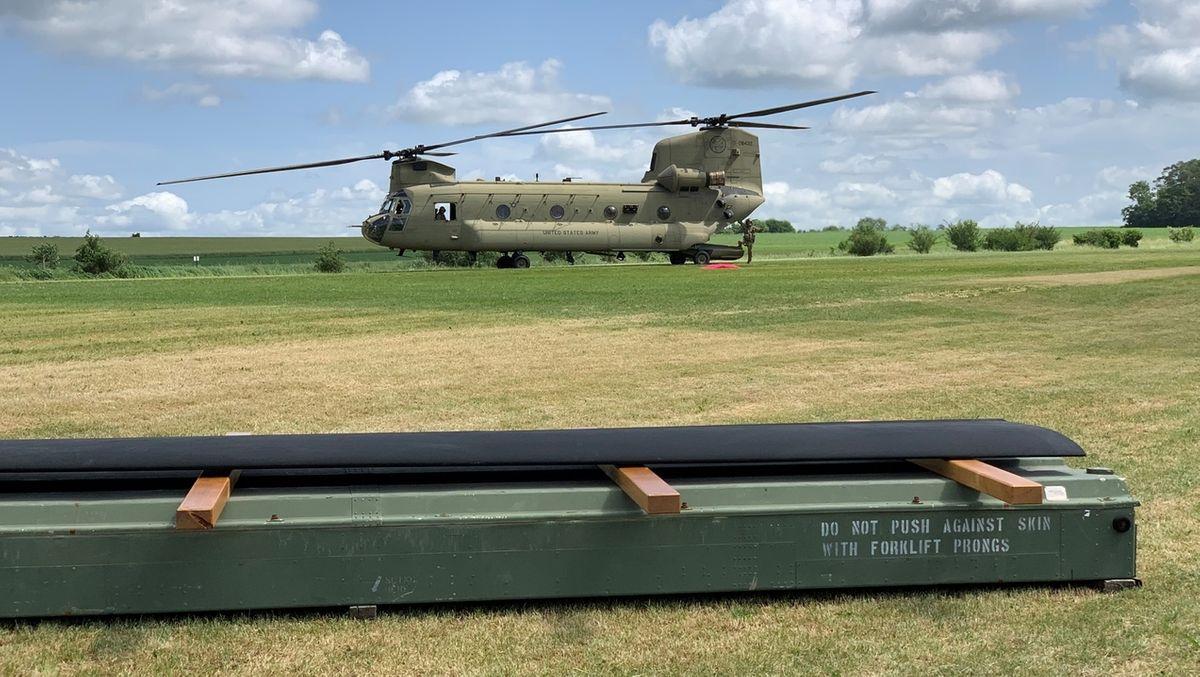 Ein Hubschrauber mit zwei Rotoren steht auf einem Feld, davor ein Rotorblatt, das die US-Army der Stadt Pegnitz schenkt.