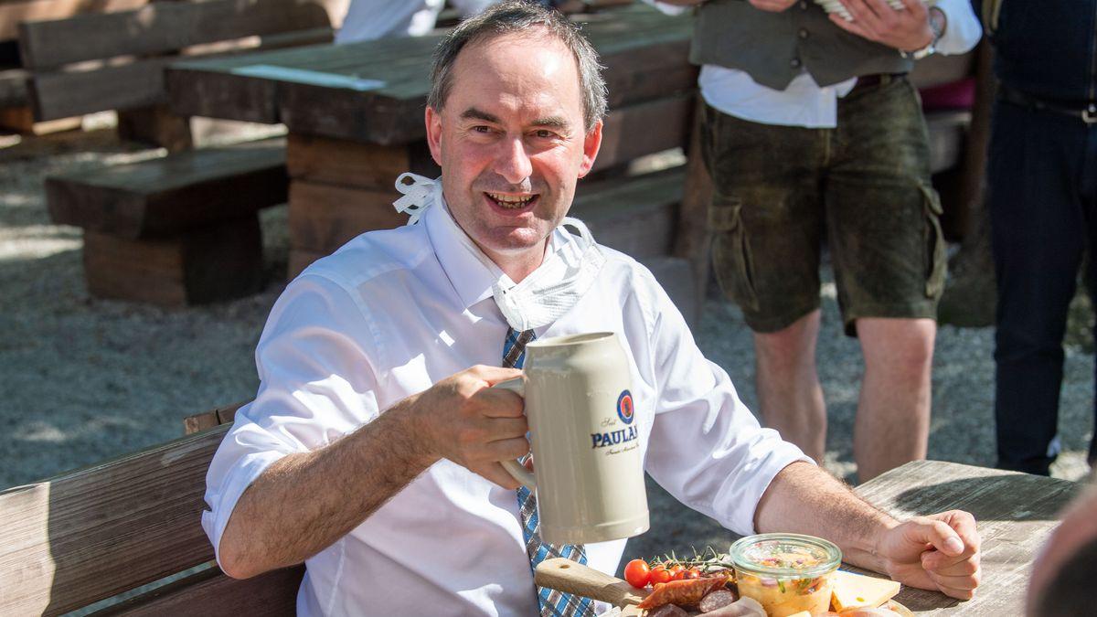 18.05.2020, Bayern, München: Hubert Aiwanger (Freie Wähler) sitzt vor einer Brotzeit am Biertisch in einem Biergarten und Prostet zu.