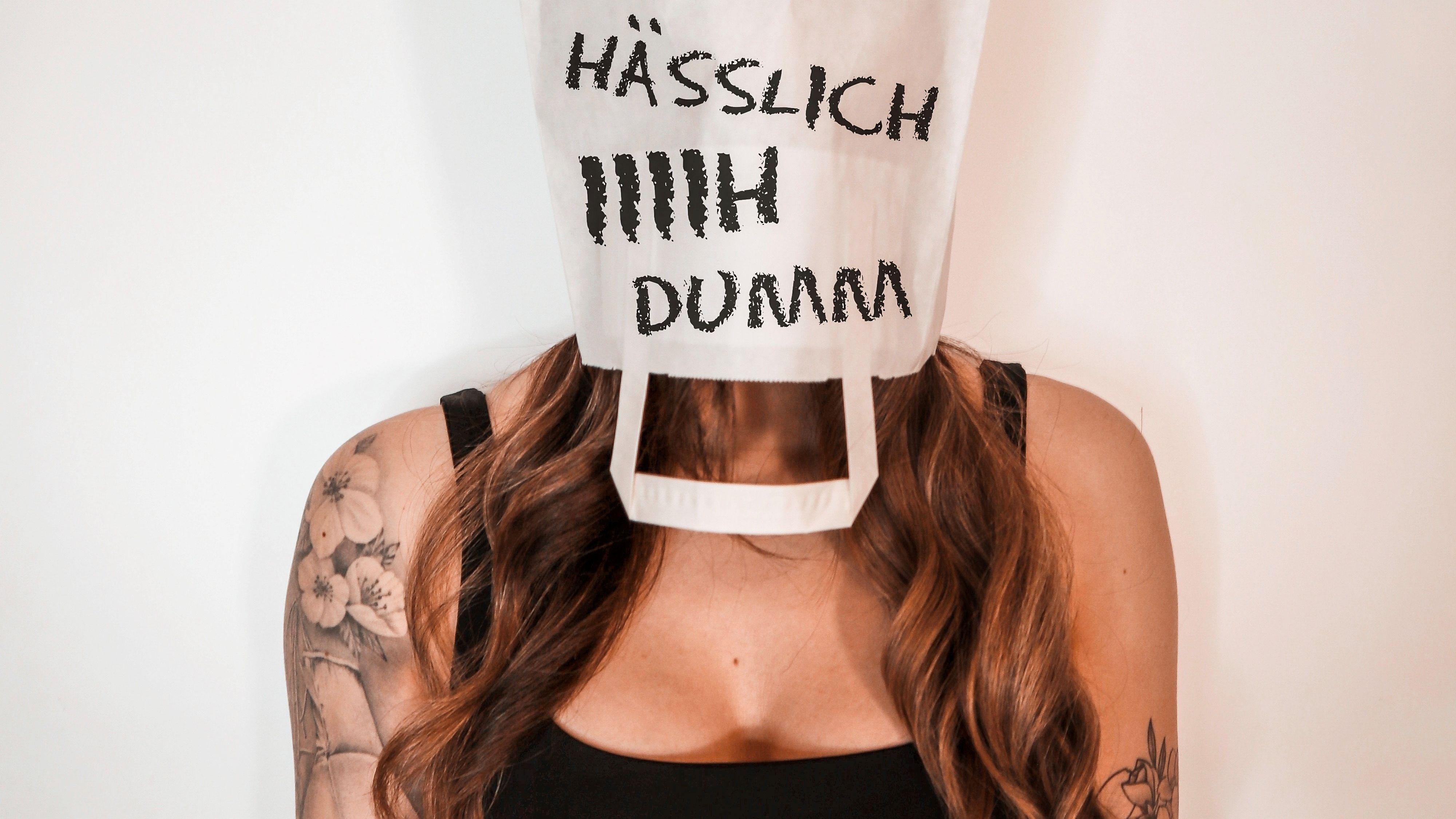 """Eine Frau mit einer Papptüte über dem Kopf, darauf die Worte """"hässlich"""", """"iiiih"""", """"dumm"""""""