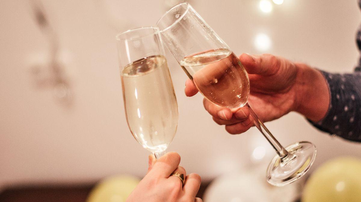 Eine Frau und ein Mann stoßen auf einer Party mit Sektgläsern auf einen bestimmten Anlass an.
