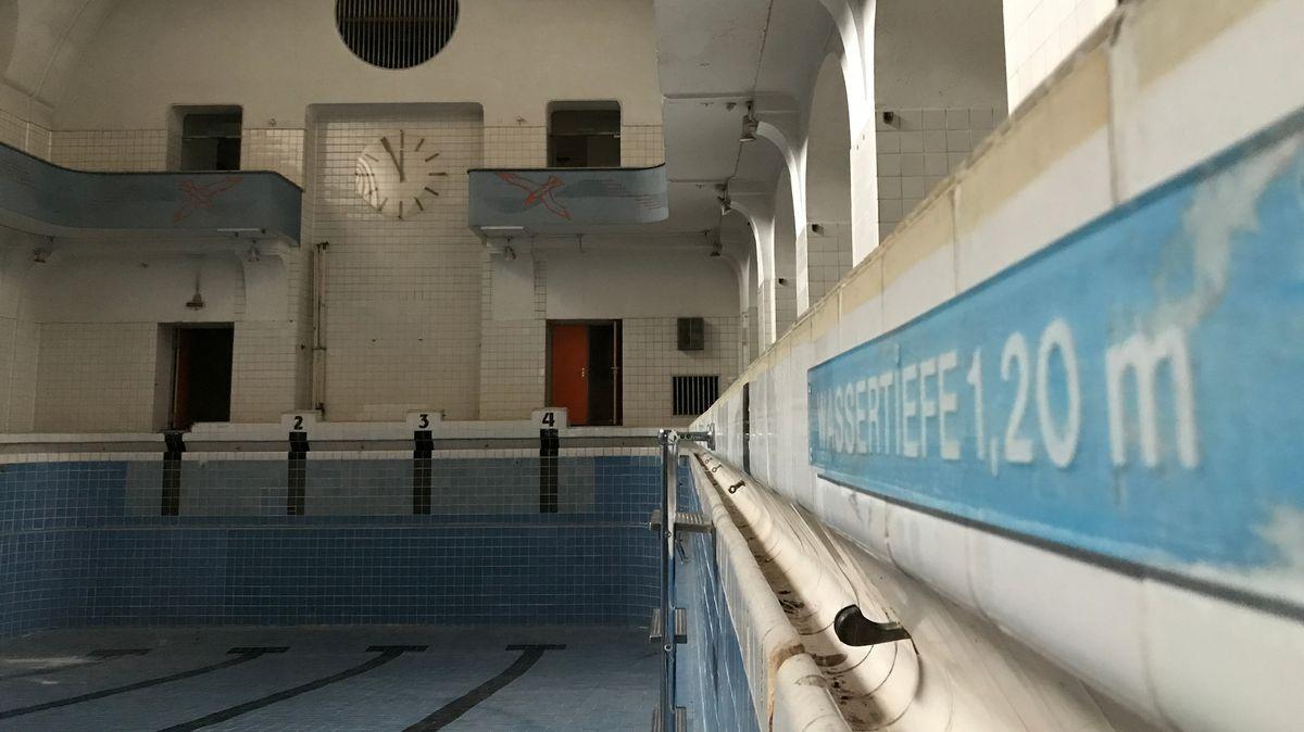 Leeres Schwimmbecken im Volksbad Nürnberg mit Blick auf eine Uhr, die 5 vor 12 anzeigt.