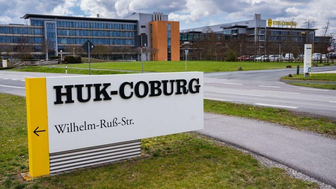 Auf einem Schild vor einem Gebäudes der Versicherungsgruppe HUK-Coburg ist der Schriftzug des Unternehmens angebracht.