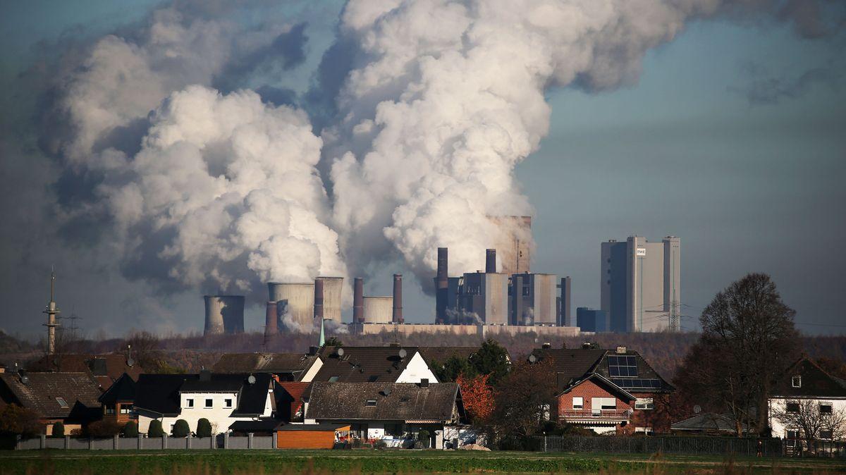 Hinter einer Wohnsiedlung bei Bergheim steigt Dampf aus dem Braunkohlekraftwerk Niederaußem des Energieversorgungskonzerns RWE.