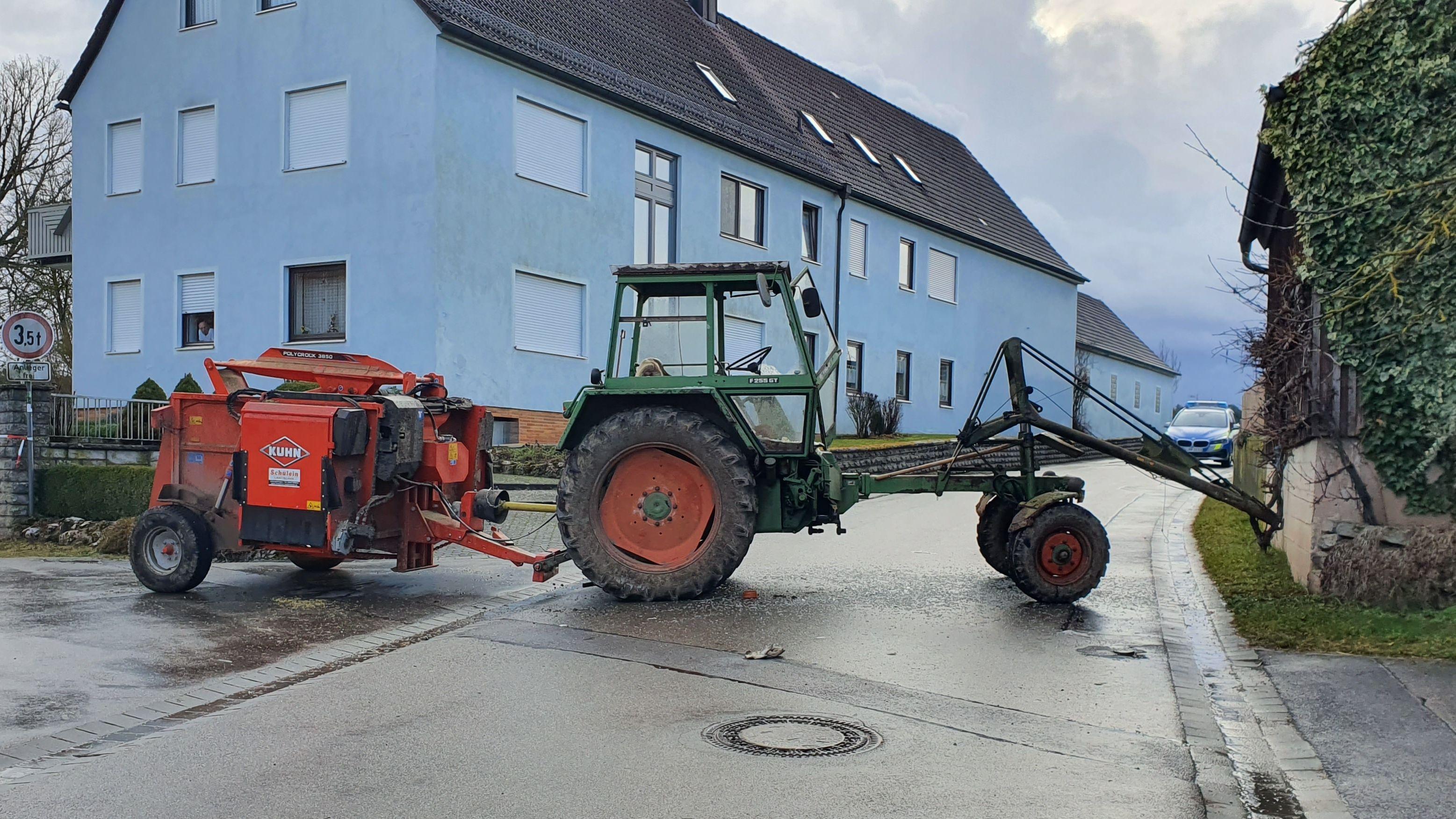 Ein Traktor samt Anhänger steht quer auf der Straße