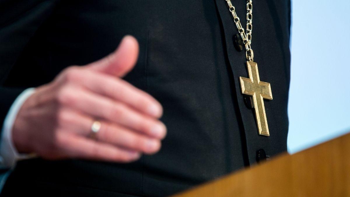 Ein Pfarrer steht an einem Redepult und hat ein Kreuz an einer Kette um den Hals.