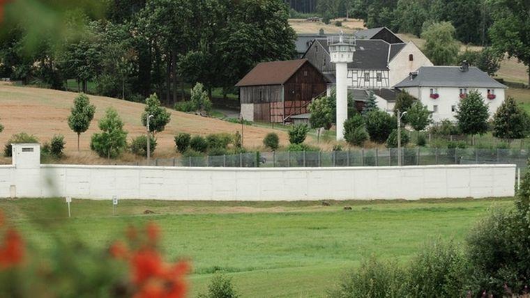 Eine lange, weiße Mauer zieht sich durch ein Dorf, im Hintergrund ein Wachturm und Häuser