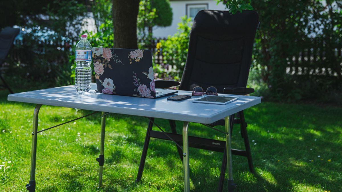 Ein Arbeitsplatz im Grünen: ein Tisch mit Laptop und Tablet steht in einem Garten.