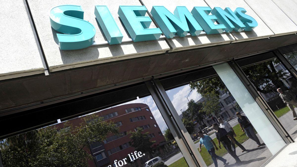 Siemens Gebäude mit großen Siemens-Schriftzug. In einer Glasscheibe spiegeln sich Passanten.