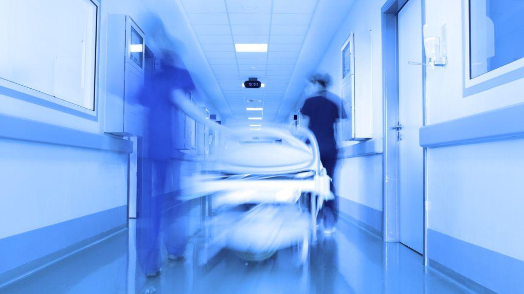 Ein Krankenbett wird durch einen Gang im Krankenhaus geschoben.