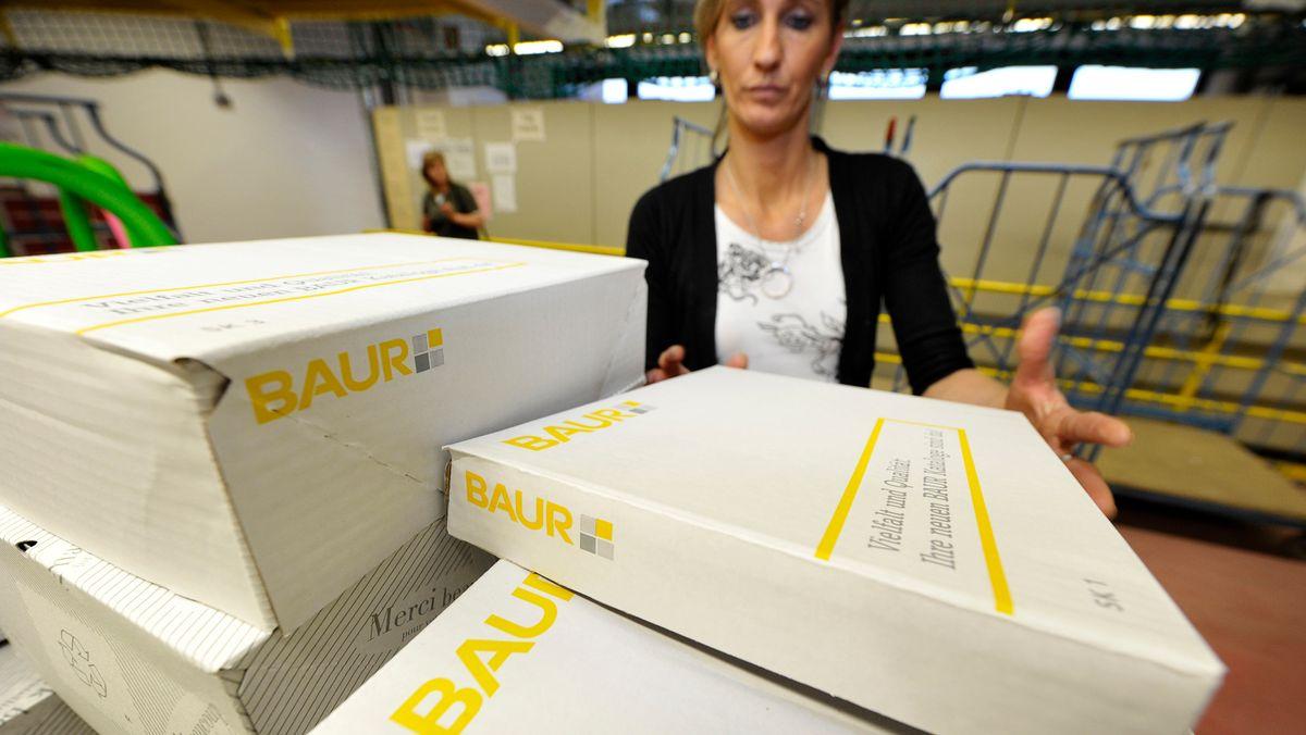 Eine Baur-Mitarbeiterin stapelt im Versand des Baur-Standortes in Burgkunstadt Kartons.