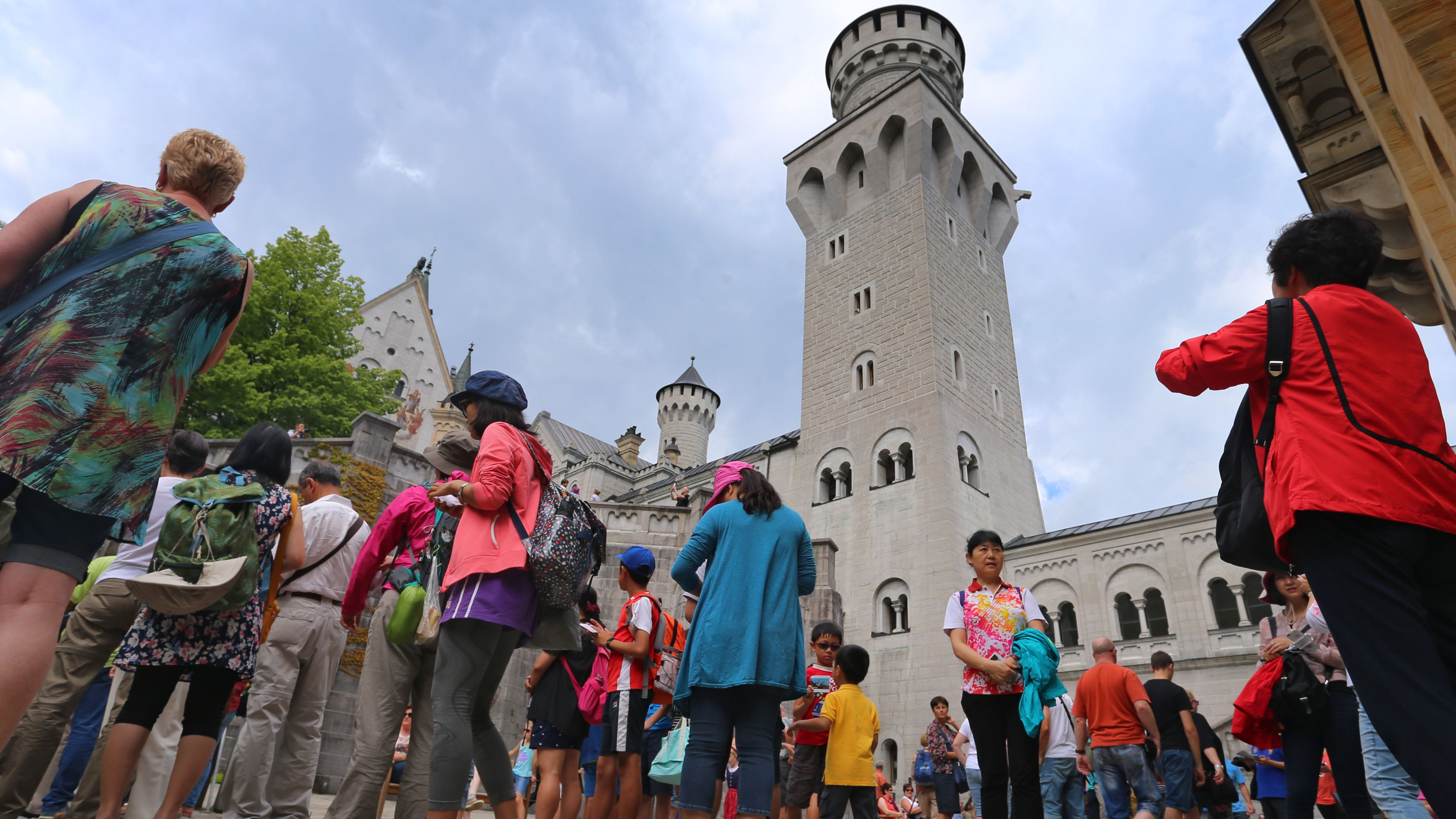 Touristen stehen im Innenhof des Schlosses Neuschwanstein bei Füssen