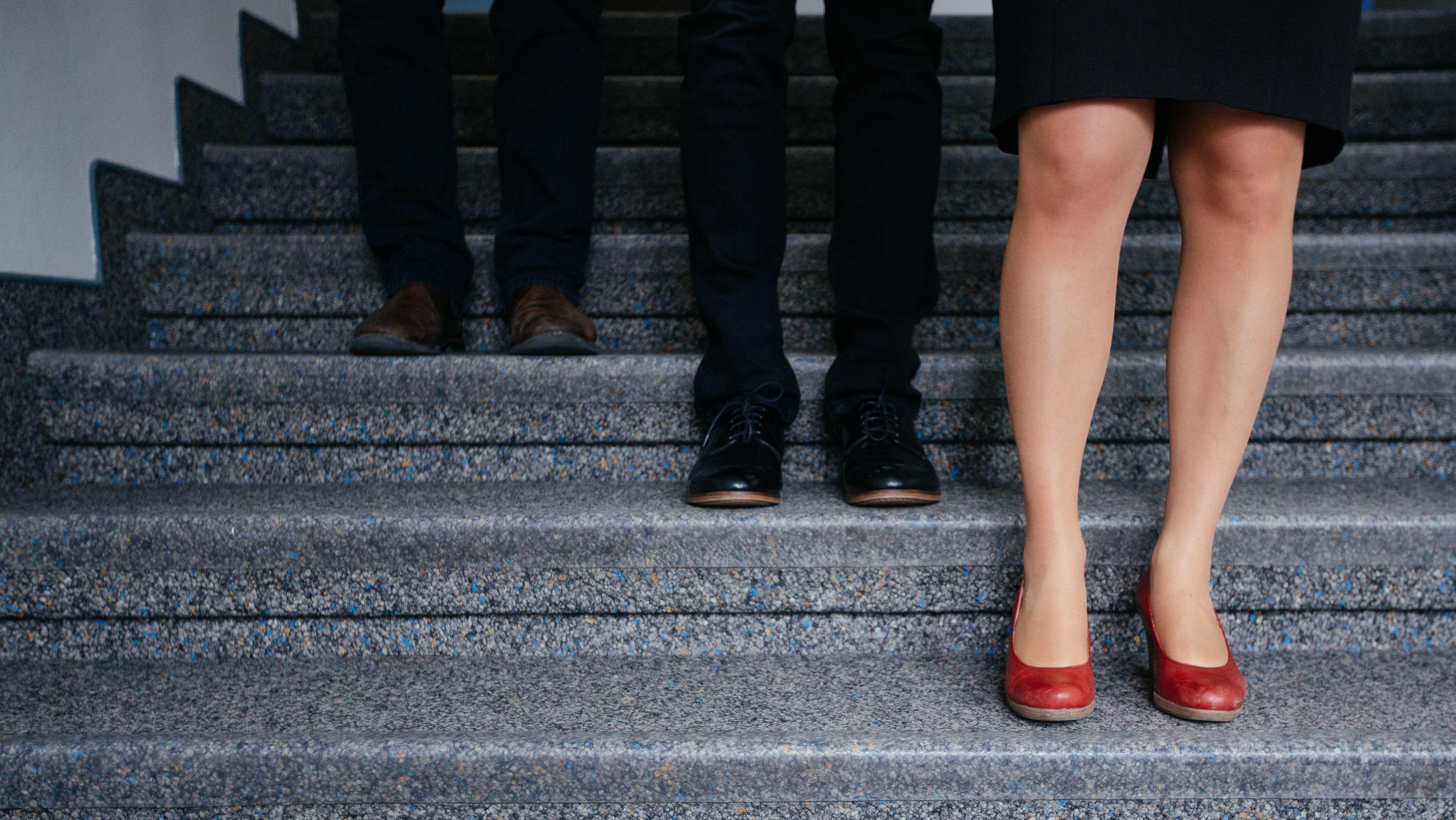In einem Treppenhaus stehen abgestuft die Beinpaare zweier Männer und einer Frau, jeweils auf einer Stufe: die Männerbeine oben, die Frauenbeine auf der untersten Stufe