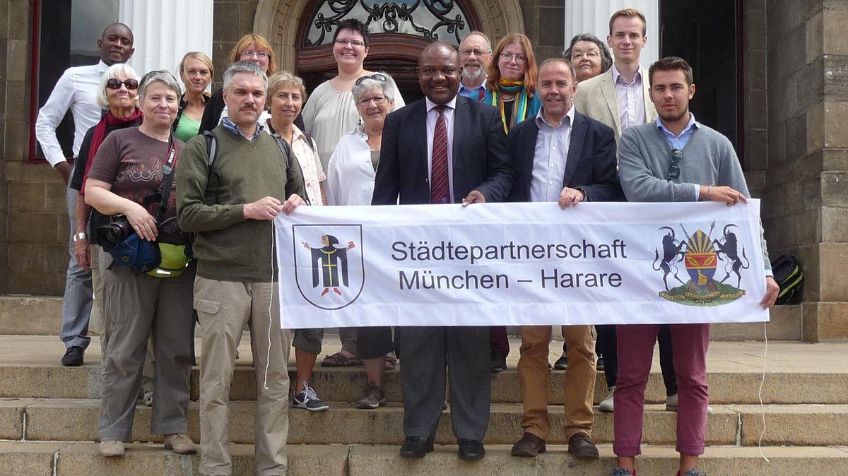 Die Mitglieder des Arbeitskreises HaMuPa stehen mit dem damaligen Bürgermeister und einem Banner, auf dem Städtepartnerschaft München - Harare steht, auf den Treppen des Rathauses von Harare.