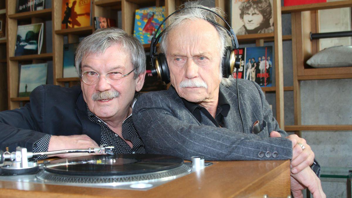 Zwei ältere Männer sitzen dicht gedrängt an einem Plattenspieler.