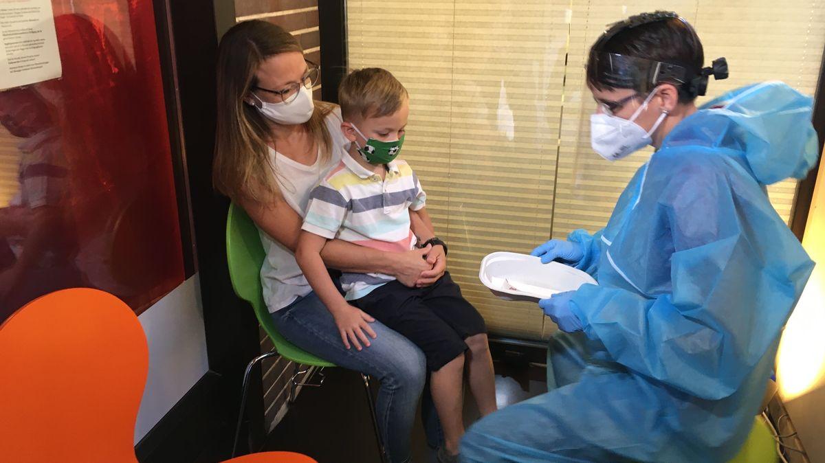 Ein Kind sitzt auf dem Schoß seiner Mutter, eine Frau in Schutzausrüstung nimmt einen Abstrich.