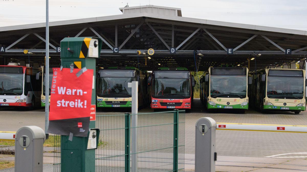 """Busse stehen in einer Garage. Davor hängt ein Schild mit der Aufschrift """"Warnstreik""""."""