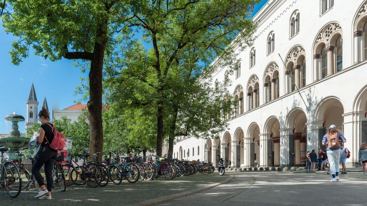 Das Hauptgebäude der LMU München am Geschwister-Scholl-Platz, rechts die Fassade, links der Platz mit Brunnen und davor viele Fahrräder.