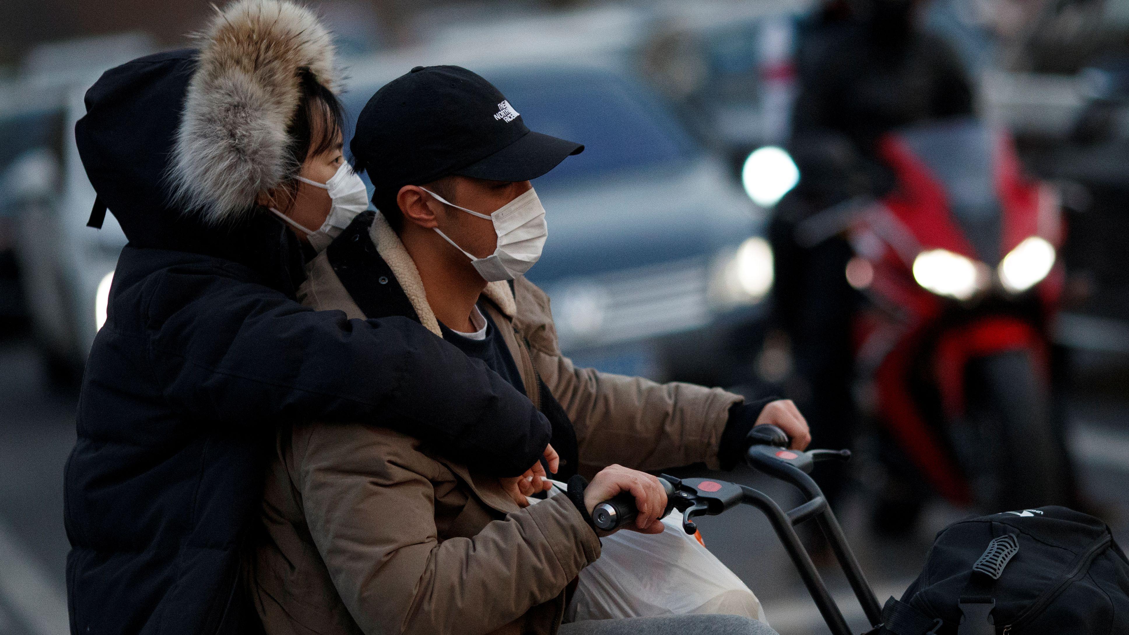 Paar fährt mit seinen Einkäufen auf einem Roller durch Peking