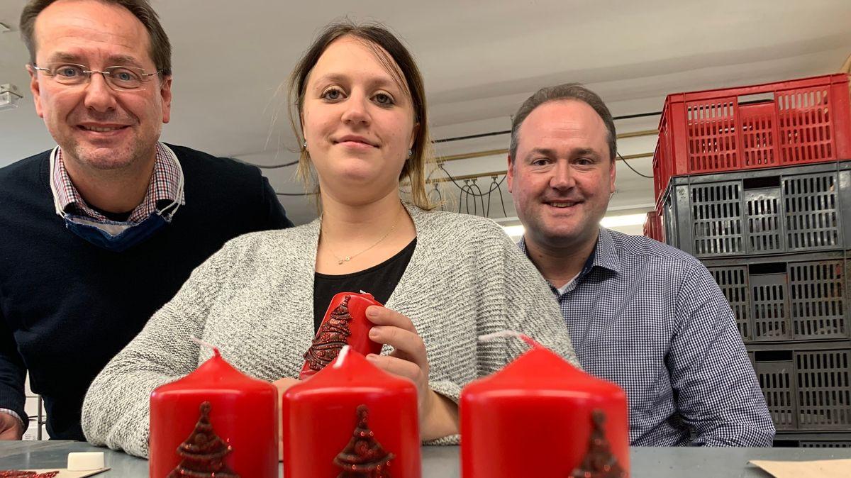 Alexander Kopschitz, die Mitarbeiterin Marina Stapfer und Christian Kopschwitz vor roten Weihnachtskerzen