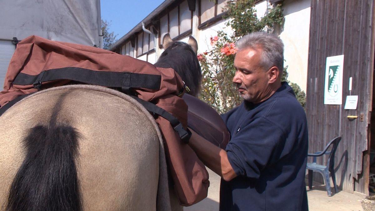 Ein Mann hebt einen Sattel auf ein Pferd.