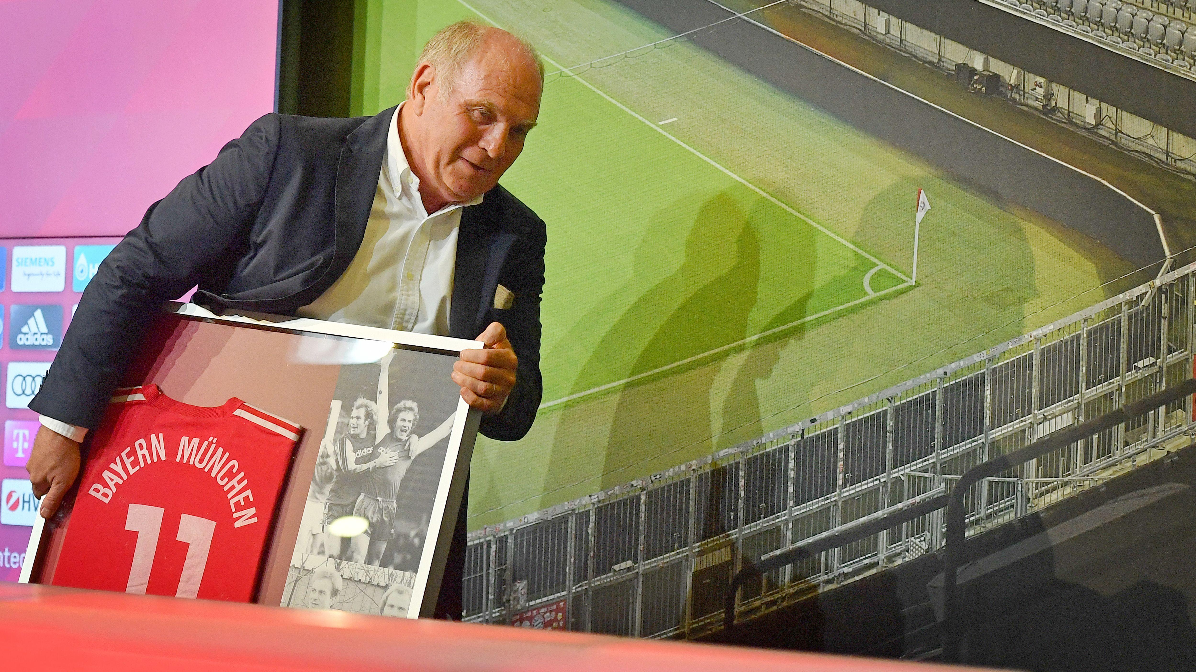 Der scheidende Bayern-Präsident Uli Hoeneß mit einem Bilderrahmen, in dem ein Foto von ihm als Spieler sowie ein altes Trikot stecken