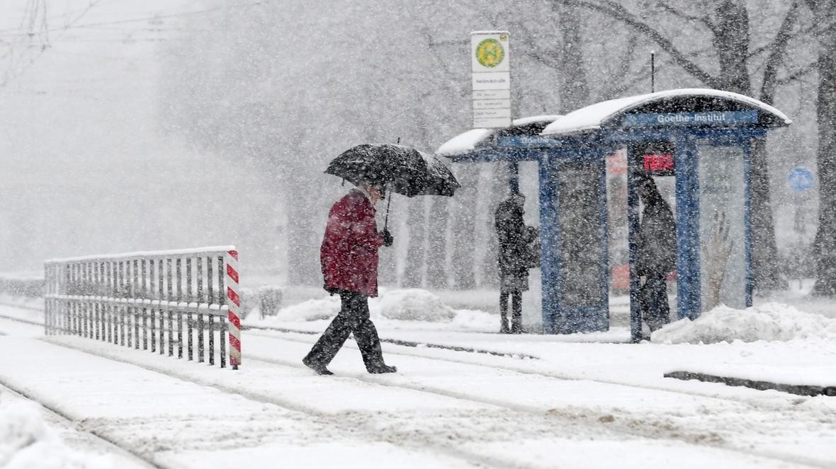 Eine Frau geht bei Schneefall über Straßenbahngleise und hat einen Regenschirm bei sich.