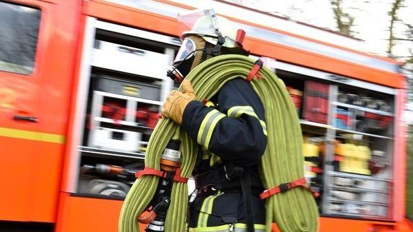 Symbolbild: Feuerwehrmann vor Feuerwehrauto